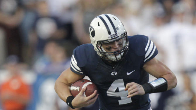 Brigham Young quarterback Taysom Hill drags Hawaii linebacker Art Laurel as he carries the ball in the first quarter of an NCAA college football game Friday, Sept. 28, 2012, in Provo, Utah. (AP Photo/Rick Bowmer)