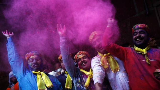 Hindu devotees daubed in colour throw coloured powder inside the Bankey Bihari temple during Holi celebrations in Vrindavan