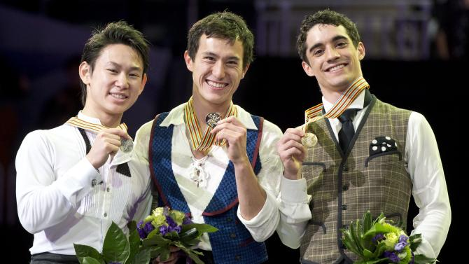 Gold medalist Patrick Chan, center, of Canada, flanked by silver medalist Dennis Ten, left, of Kazakstan, and bronze medalist Javier Fernandez, of Spain, show off their medals during the flower ceremony in the men's competition at the World Figure Skating Championships Friday, March 15, 2013 in London, Ontario. AP Photo/The Canadian Press, Paul Chiasson)