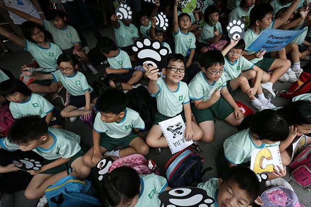 Children in Singapore waiting for the arrival of pandas. (Getty Images)