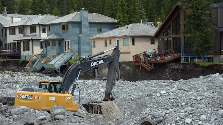 An excavator works on the Cougar Creek bed in Canmore, Alberta, Canada on Saturday, June 22, 2013 after flooding which devastated much of southern Alberta province. (AP Photo/The Canadian Press, Jonathan Hayward)