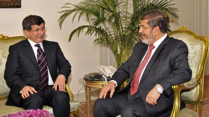 "In this image released by the Egyptian President, Egyptian President Mohammed Morsi, right, meets with  Turkish Foreign Minister Ahmet Davutoglu at the Presidential Palace in Cairo, Egypt, Monday, Sept. 17, 2012.  Turkey, which hosts some 80,000 Syrian refugees, has accused Syria of ""state terrorism"" and has allowed rebels to use its territory as a base. (AP Photo/Egyptian Presidency)"