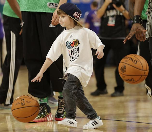 A child dribbles the ball before the NBA All Star basketball game, Sunday, Feb. 16, 2014, in New Orleans