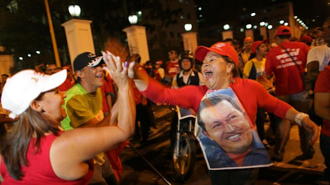 Supporters of Venezuela's President Hugo Chavez cheer after polling stations closed and before any results were made available in Caracas, Venezuela, Sunday, Oct. 7, 2012. Venezuela's electoral council says Chavez has won re-election, defeating challenger Henrique Capriles. (AP Photo/Rodrigo Abd)