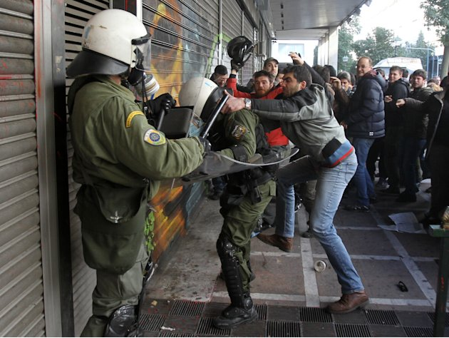 Protesters clash with riot police outside the Labor Ministry in Athens, Wednesday, Jan. 30, 2013. Protesters from a Communist-back labor union forced their way into a government building and clashed w