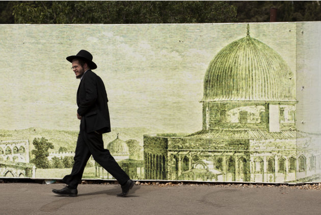 An ultra-Orthodox Jewish man walks past a sign depicting the Dome of the Rock Mosque, in Jerusalem, Sunday, May 19, 2013. (AP Photo/Sebastian Scheiner)