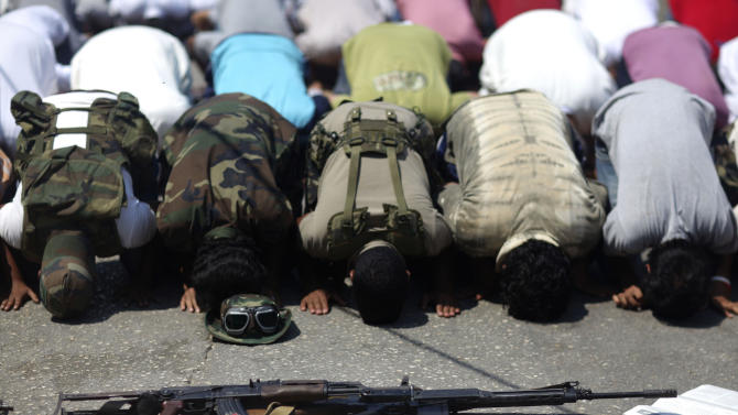 Rebel fighters, foreground, pray during Friday prayers in the rebel-held town of Benghazi, Libya, Friday, Aug. 19, 2011. (AP Photo/Alexandre Meneghini)