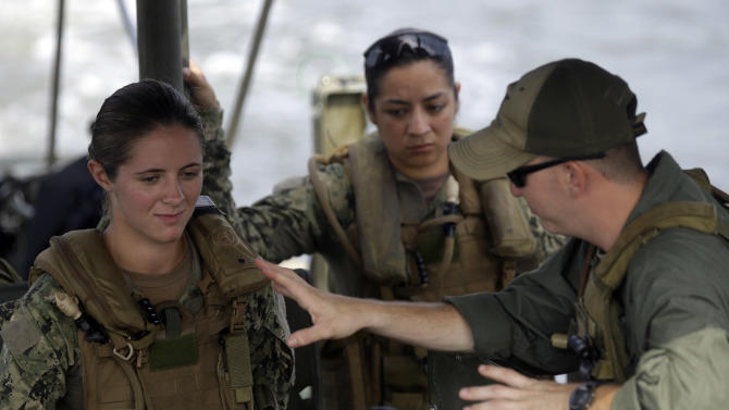 In this photo taken Tuesday, Aug. 13, 2013 U.S. Navy Master-at-Arms Third Class Danielle Hinchliff, left, and Master-at-Arms Third Class Anna Schnatzmeyer, both of Coastal Riverine Squadron 2, train under the watchful eye of instructor Boatswain's Mate Second Class Christopher Johnson, right, while training on a Riverine Assault Boat as they participate in a U.S. Navy Riverine Crewman Course at the Center for Security Forces Learning Site at Camp Lejeune, N.C. This is the first time female participants have received this training as women begin to take on combat roles in the military. (AP Photo/Gerry Broome)