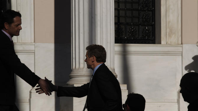 International Monetary Fund (IMF) mission chief Poul Thomsen, shakes hands with an unidentified official as he arrives for a meeting between Greek Prime Minister Antonis Samaras, Finance Minister Yannis Stournaras and debt inspectors from the European Central Bank, European Commission and IMF, known as the troika, in Athens, Tuesday, June 18, 2013. Greece depends on international bailouts conditional on harsh austerity measures. Its fragile governing coalition is in disarray, over a decision by the majority conservatives to close state ERT broadcaster to save money. (AP Photo/Kostas Tsironis)