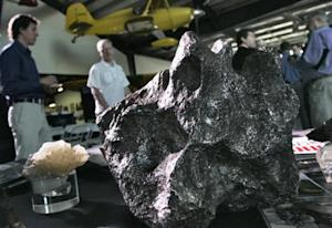 Meteorites sit on a display table at the Deep Space Industries announcement of plans for the world's first fleet of commercial asteroid-prospecting spacecraft in Santa Monica, California