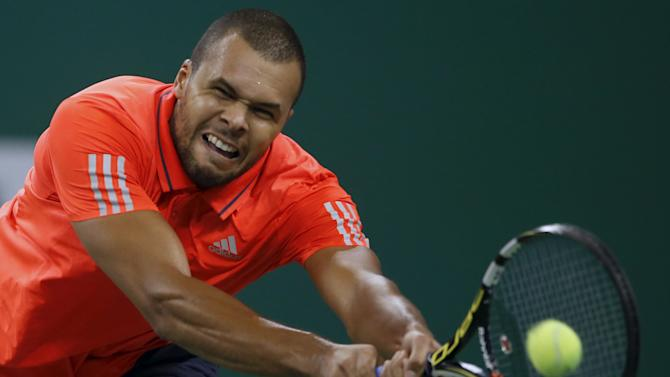 Jo-Wilfried Tsonga of France returns a shot to Victor Estrella Burgos of Dominican Republic during their men's singles match at the Shanghai Masters tennis tournament in Shanghai