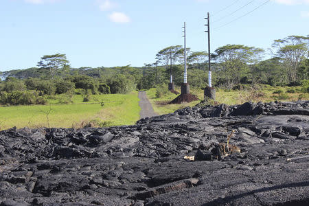 Lava flow from the Kilauea volcano is pictured having crossed Cemetery Road, on Hawaii's Big Island