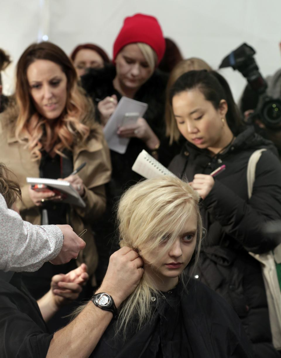 Fashion journalists take notes backstage as a model's hair is styled before the Tadashi Shoji Fall 2013 collection is modeled during Fashion Week in New York,  Thursday, Feb. 7, 2013. (AP Photo/Richard Drew)