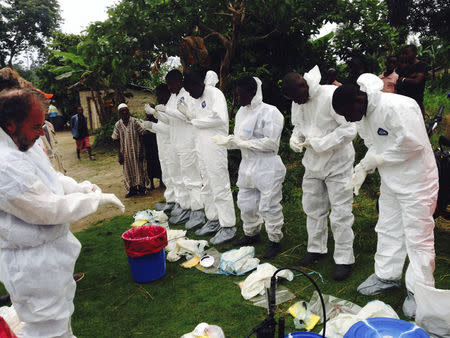 Volunteers prepare to remove the bodies of people who were suspected of contracting Ebola and died in the community in the village of Pendebu