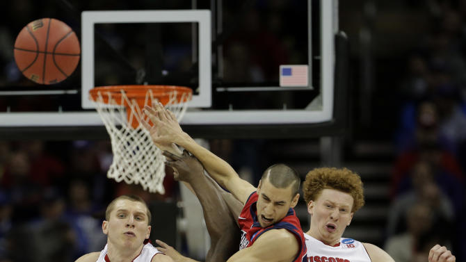 Mississippi guard Marshall Henderson, center, battles Wisconsin forward/center Jared Berggren (40) and forward Mike Bruesewitz (31) for a rebound during the second half of a second-round game of the NCAA college basketball tournament Friday, March 22, 2013, in Kansas City, Mo. (AP Photo/Charlie Riedel)