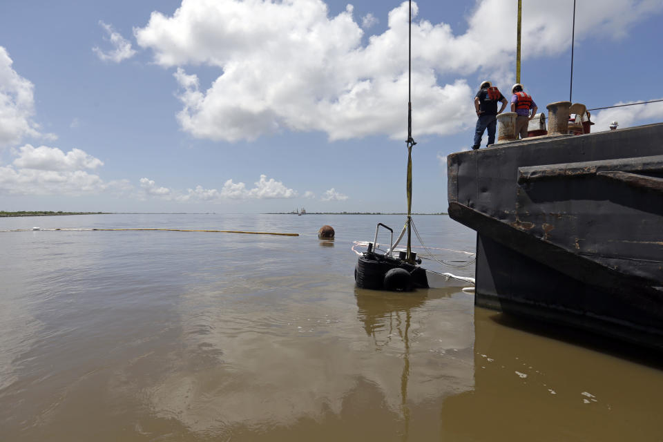 "Workers raise ""C-Pec,"" the 47 foot tugboat which sank Saturday in the middle of the Mississippi River, near Venice, La., Wednesday, July 10, 2013. (AP Photo/Gerald Herbert)"