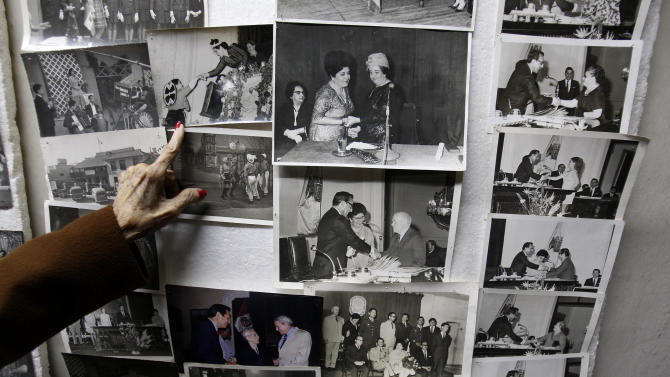 "In this Nov. 26, 2012 photo, journalist and radio host Maria Julia Venegas, better known as Maruja Venegas, 97, points to pictures of herself during an interview at her home in Lima, Peru. Venegas who began broadcasting ""Radio Club Infantil,"" a show for Peru's children in the golden age of radio and World War II, has earned a citation from Guinness World Records as the globe's longest-running radio personality. (AP Photo/Karel Navarro)"