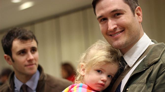Nicholas J. Van Sickels, right, stands with his husband, Andrew S. Bond, and holds their adopted daughter, Jules, 2, before a news conference in New Orleans about a federal lawsuit filed Wednesday, Feb. 12, 2014, to challenge the Louisiana Constitution's ban on recognizing same-sex marriages performed in states where they are legal. They are among four couples, all married states where same-sex marriage is legal, who joined the Forum for Equality Louisiana in a suit against the state registrar and state revenue secretary. (AP Photo/Janet McConnaughey)