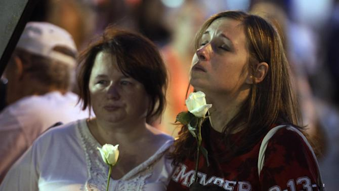 Tamiko Schaefer, of Melbourne, Fla., right, and Lacey Grabek, of Noblesville, Ind., reflect during a moment of silence for the seven people killed and dozens injured when stage rigging collapsed at the Indiana State Fair in Indianapolis a year ago, Monday, Aug. 13, 2012. (AP Photo/Michael Conroy)