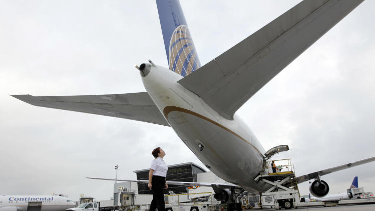 FILE - In this April 16, 2010 file photo, Continental Airlines First Officer Pamela Perdue conducts a pre-flight inspection of a 767 airplane at George Bush Intercontinental Airport Friday in Houston. United Continental reports quarterly financial results before the market opens on Thursday, April 25, 2013. (AP Photo/David J. Phillip, file)