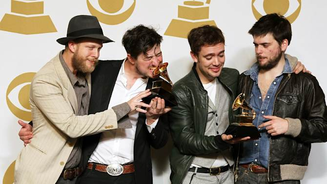 """Members of the musical group Mumford & Sons, from left, Ted Dwane, Marcus Mumford, Ben Lovett and Winston Marshall, pose backstage with the best long form music video award for """"Big Easy Express"""" and the album of the year award for """"Babel"""" at the 55th annual Grammy Awards on Sunday, Feb. 10, 2013, in Los Angeles. (Photo by Matt Sayles/Invision/AP)"""
