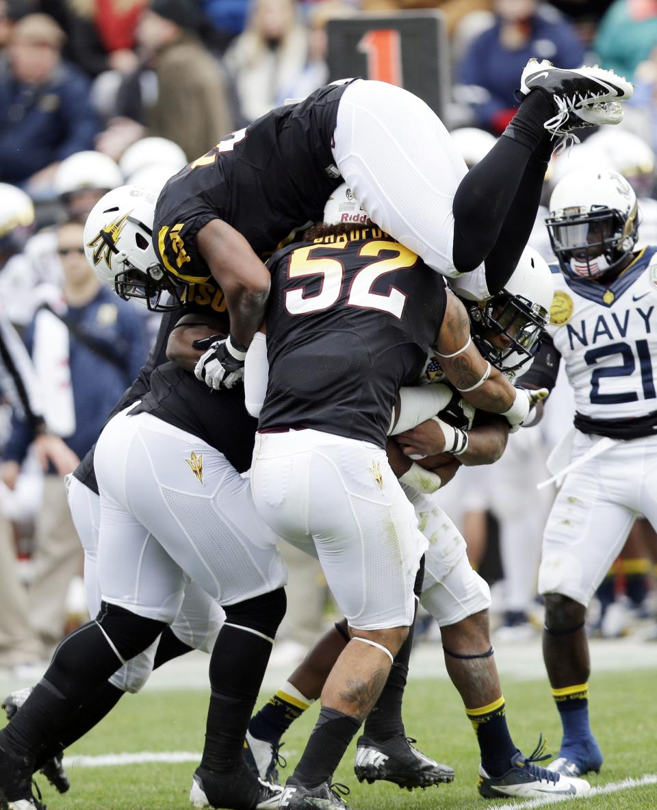 Navy fullback Noah Copeland, second from right, is tackled by a group of Arizona State defenders during the first half of the Fight Hunger Bowl NCAA college football game in San Francisco, Saturday, Dec. 29, 2012. (AP Photo/Marcio Jose Sanchez)