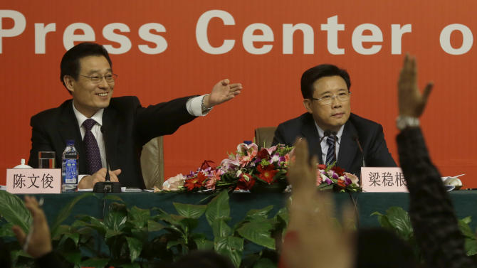 "Moderator Chen Wenjun, left, invites questions from reporters next to Liang Wengen, Chairman of the board of the SANY Group at a press conference with the theme of ""implementing innovation strategies to accelerate transformation and development"" as part of the 18th Communist Party Congress at the media centre in Beijing, Saturday, Nov. 10, 2012. (AP Photo/Ng Han Guan)"
