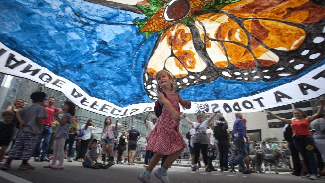 "A girl dances under a protest parachute as people take part in the ""People's Climate March"" down 6th Ave. in the Manhattan borough of New York"