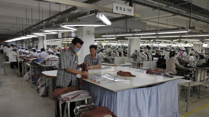In this photo taken on Sept. 21, 2012, two North Korean men working for ShinWon, a South Korean clothing maker, prepare garments for production at a factory in Kaesong, North Korea. Since April 3, North Korean authorities have barred South Koreans, including ShinWon managers, from entering North Korea through the Demilitarized Zone to get to the Kaesong industrial complex where some 120 South Korean companies run factories employing North Korean workers. (AP Photo/Jean H. Lee)