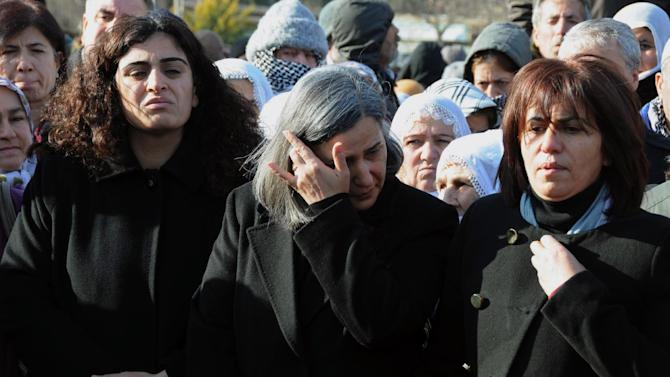 "Several hundreds Turkish Kurds, including lawmakers Sebahat Tuncel, left, and Gultan Kisanak, center, gather to protest the killings of three Kurdish women in Paris, France, in southeastern Turkish city of Diyarbakir, Turkey, Thursday, Jan. 10, 2013. The three women were ""executed"" at a Kurdish center in Paris, French Interior minister Manuel Valls said Thursday. (AP Photo)"