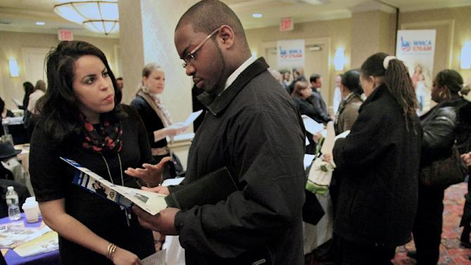 In this Jan. 25, 2012 photo, Daniela Silvero,left, an admissions officer at ASA College, discuss job opportunities with Patrick Rosarie, who is seeking a job in IT, during JobEXPO's job fair, in New York. The unemployment rate fell for the fifth straight month after a surge of January hiring, a promising shift in the nation's outlook for job growth. (AP Photo/Bebeto Matthews)
