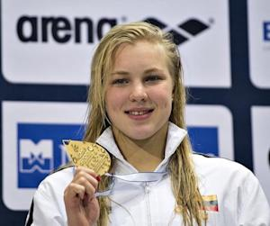 Meilutyte of Lithuania poses with her gold medal after winning the women's 100m Medley final during the LEN European Short Course Swimming Championship in Herning