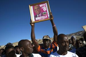 Supporters of Haitian President Michel Martelly wave …
