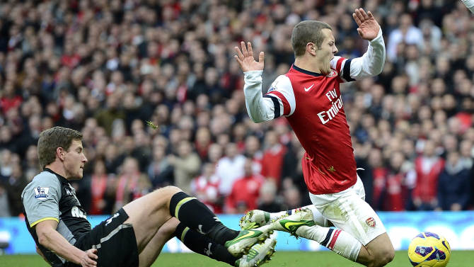 Arsenal's Jack Wilshere is challenged by Tottenham Hotspur's Jan Vertonghen during their English Premier League soccer match at the Emirates stadium in London