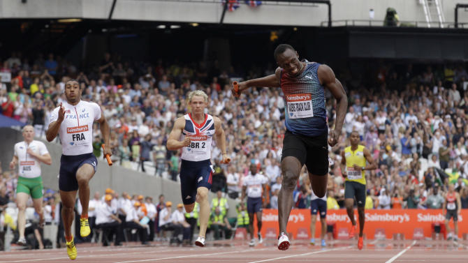 Jamaica's Usain Bolt, right, crosses the line to win the men's 400m relay for his team Racers Track Club during the Diamond League athletics meet at the stadium in the Queen Elizabeth Olympic Park, London, Saturday, July 27, 2013. The athletics meet marks the anniversary of the London 2012 Olympic Games. (AP Photo/Matt Dunham)