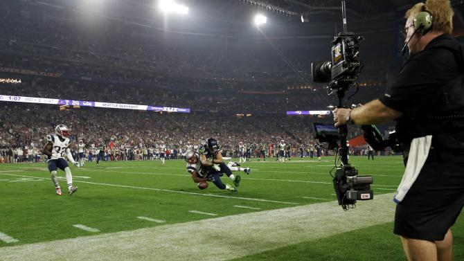 An NBC television cameraman covers from the sideline as the Seattle Seahawks and the New England Patriots play during the NFL Super Bowl XLIX football game in Glendale