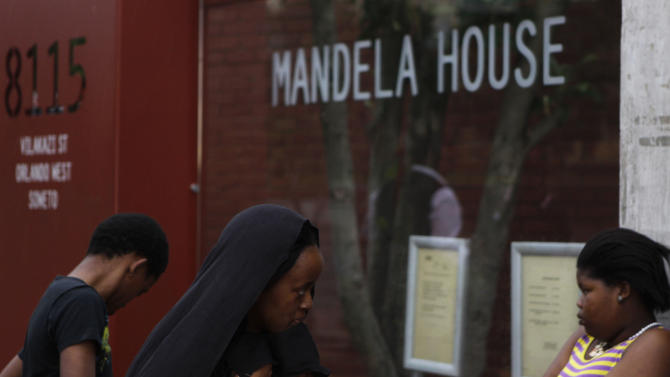 "People visit former South African president Nelson Mandela's Soweto, home, turned-museum,  in Soweto, Sunday Dec. 9, 2012. South Africans prayed Sunday for the health of former President Nelson Mandela and anxiously awaited further word about the anti-apartheid leader after he was admitted to a military hospital. President Jacob Zuma visited Mandela Sunday morning at the hospital in Pretoria and found the frail 94-year-old to be ""comfortable and in good care,"" presidential spokesman Mac Maharaj said in a statement. Maharaj offered no other details about Mandela, nor what medical tests he had undergone since entering the hospital Saturday. (AP Photo/Denis Farrell)"