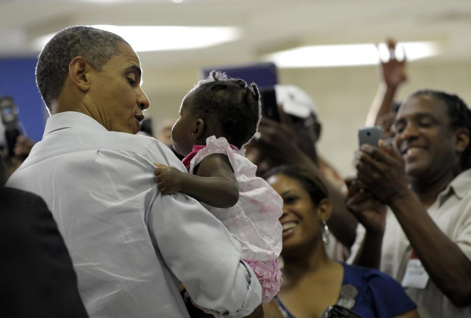 President Barack Obama holds a baby as he greets the overflow crowd before a campaign event at Green Run High School in Virginia Beach, Va., Friday, July 13, 2012. Obama is spending the day in Virginia campaigning. (AP Photo/Susan Walsh)