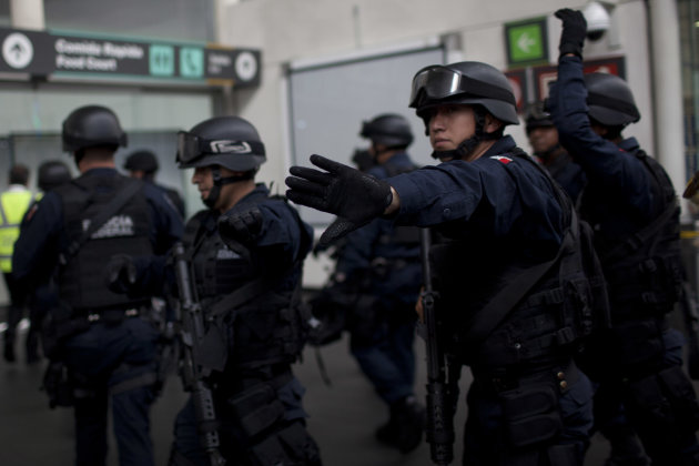 Mexico&#39;s Federal Police officers arrive to the scene where a shooting took place in Mexico City&#39;s international airport on Monday, June 25, 2012. Two people were shot to death and one was wounded at one of the airport&#39;s terminal and according to the federal Public Safety Department, at least one was an officer. Details of the shooting are still unclear. (AP Photo/Alexandre Meneghini)