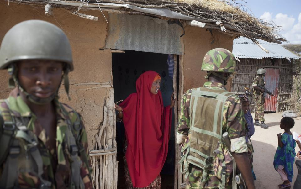 A female Somali villager talks to Kenyan army soldiers in Tabda, inside Somalia Monday, Feb. 20, 2012. Kenya's military has been fighting inside Somalia in an ongoing offensive against militant group al-Shabab since October, when Somali gunmen carried out several kidnappings in Kenya. (AP Photo/Ben Curtis)