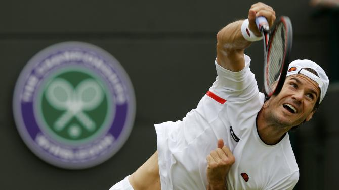Tommy Haas of Germany serves during his match against Milos Raonic of Canada at the Wimbledon Tennis Championships in London