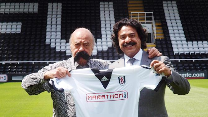 Mohamed Al Fayed, left, wearing a fake mustache, with new Fulham owner Shahid Khan, during a photo call at Craven Cottage, London, Saturday July 13, 2013.(AP Photo/PA, Max Nash)UNITED KINGDOM OUT