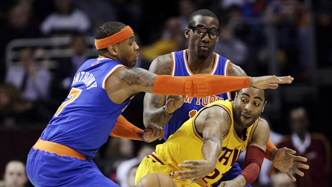 Cleveland Cavaliers' Wayne Ellington, right, passes the ball under pressure from New York Knicks' Carmelo Anthony, left, and Amare Stoudemire during the first quarter of an NBA basketball game, Monday, March 4, 2013, in Cleveland. (AP Photo/Tony Dejak)
