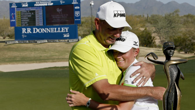 Stacy Lewis, right, gets a hug from her father, Dale Lewis, after she won the LPGA Founders Cup golf tournament on Sunday, March 17, 2013, in Phoenix. (AP Photo/Ross D. Franklin)