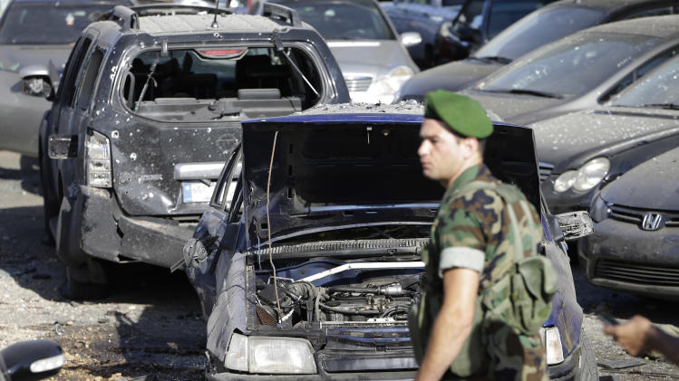 A Lebanese army soldier stands guard in front of damaged cars where a rocket struck a car exhibit at the Mar Mikhael district, south of Beirut, Lebanon, Sunday May 26, 2013. Rockets slammed Sunday into two Beirut neighborhoods that are strongholds of Lebanon's Hezbollah group, wounding at least 4 people, Lebanese security officials and media said. Tensions have been running high in Lebanon, and Syrian rebels have threatened to retaliate against the militant Shiite Hezbollah group for sending fighters to assist President Bashar Assad's forces in Syria. (AP Photo/Hussein Malla)