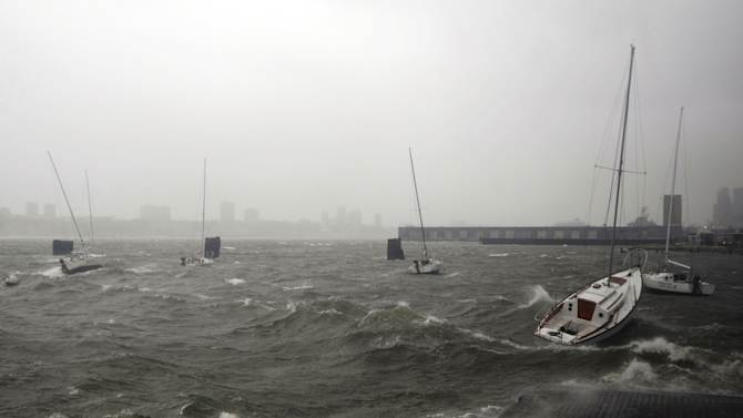 Sailboats rock in choppy water at a dock along the Hudson River Greenway during a storm, Monday, Oct. 29, 2012, in New York. Hurricane Sandy continued on its path Monday, forcing the shutdown of mass transit, schools and financial markets, sending coastal residents fleeing for higher ground, and threatening a dangerous mix of high winds and soaking rain. (AP Photo/Jeffrey Furticella)