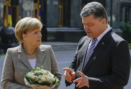 Merkel looks on as Poroshenko gestures in Kiev