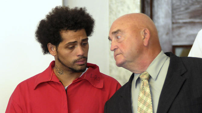 Carlos Ortiz, left, stands in Attleboro District Court with attorney John Connors, right, for his arraignment on weapons charges, Friday, June 28, 2013 in Attleboro, Mass. Ortiz was arrested Wednesday in Bristol, Conn., in connection with the murder case against former New England Patriots tight end Aaron Hernandez , now charged in the murder of Odin Lloyd. (AP Photo/The Sun Chronicle, Mark Stockwell, Pool)