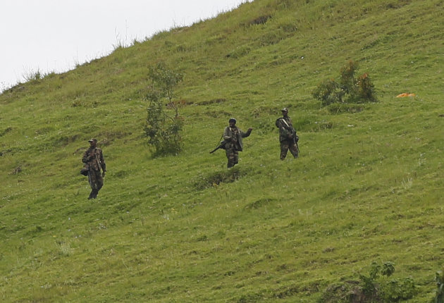 M23 rebel fighters are seen walking up a hill overlooking Goma, six kilometers from the center of the eastern Congo city, Monday Dec. 3, 2012. Rebels, who finally withdrew from this regional capital over the weekend, said they are waiting for a 48-hour deadline to expire on Monday afternoon, before deciding if they will take back the city. After a nearly two-week occupation, the M23 rebel group agreed to leave Goma on the condition that Congo's government enters into negotiations with them by 2 p.m. Monday. (AP Photo/Jerome Delay)