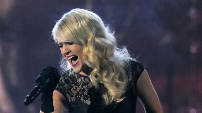 """FILE - This April 7, 2013 file photo shows Carrie Underwood performing at the 48th Annual Academy of Country Music Awards at the MGM Grand Garden Arena in Las Vegas. Underwood will pay tribute to the victims of the recent deadly tornadoes in Oklahoma in her appearance on the CMT Music Awards on Wednesday, June 5. Underwood will perform her new single """"See You Again,"""" recasting it as a somber memorial with the aid of two dozen choir members from Nashville's Christ Church. (Photo by Chris Pizzello/Invision/AP, file)"""
